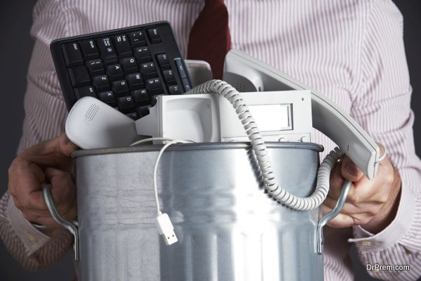Businessman Holding Garbage Can With Obsolete Office Equipment
