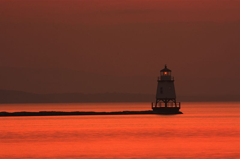 Light house in Lake Champlain at dusk, as seen from Burlington Vermont. Photo by Nagaraju.ramanna. Wikimedia Commons.
