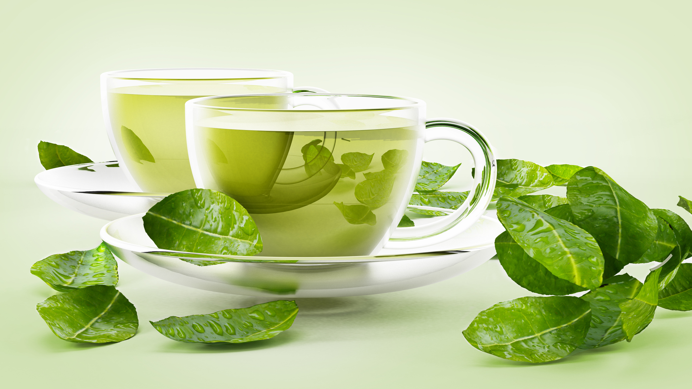 Glass cups with green tea and tea leaves isolated on white