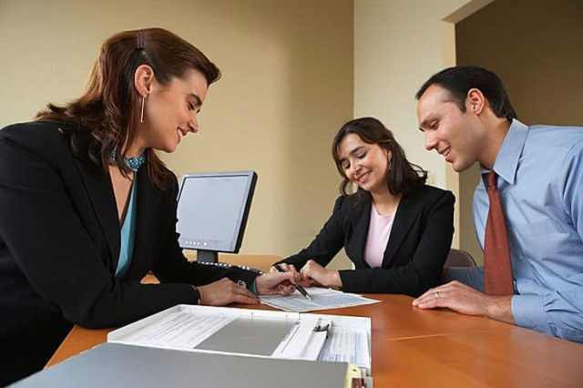 Couple talking with real estate agent at office