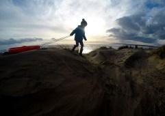 Girl Sledging On Sand Dunes