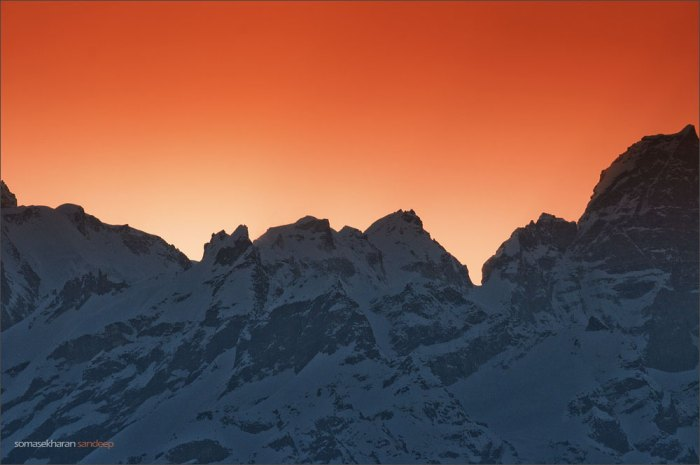 The sun rises behind a wall of snow and rock