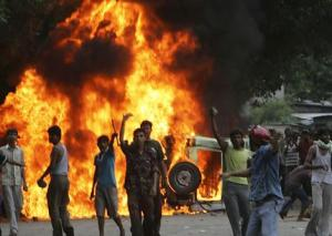 A police vehicle is set on fire by an irate crowd during a protest in the northeastern city of Siliguri