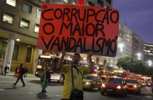 A man protests Brazilian President Dilma Rousseff's with a sign that reads,