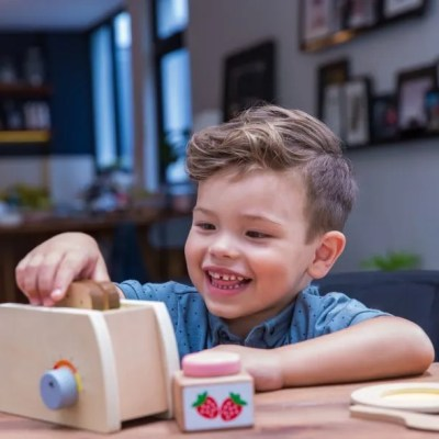 Boy playing with wooden toy toaster