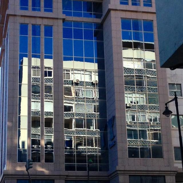 Die Spiegelung eines Wohnblocks in der Glasfront eines Geschäftsgebäudes unweit der Metro-Station 'San Sebastiao' im Príncipe Real-Vierteil in Lissabon.