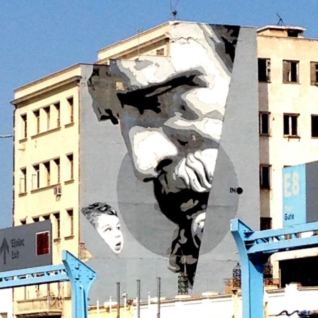 """""""We Have The Power"""" - """"Wissen ist Macht"""": ein Wandbild von iNO aus dem Jahr 2015 im Hafen von Piräus. Es zeigt ein Kind, das zu einem Portrait des antiken Philosophen Demokrit aufsieht (09/2020, Piräus, Attika, Griechenland)."""