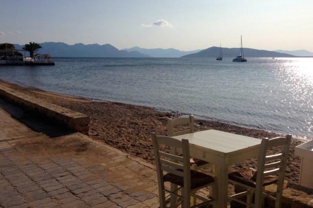 Ähnlich einem Traum ... Ein verlassener Tavernentisch, zwei wackelige, leere Holzstühle auf einer Terasse am Strand.