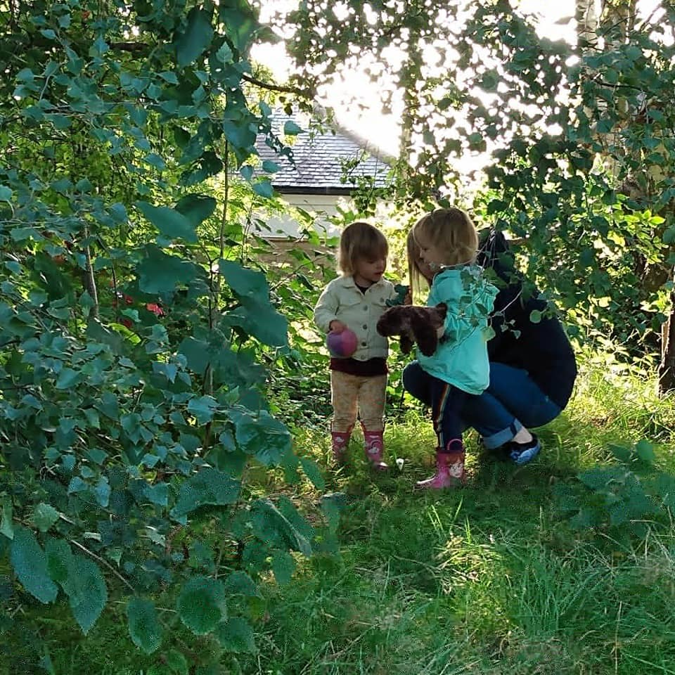 young girls with carer exploring the woods
