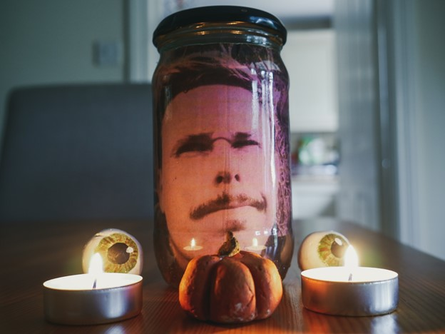 mans head in a jar with candles and mini pumpkin in front