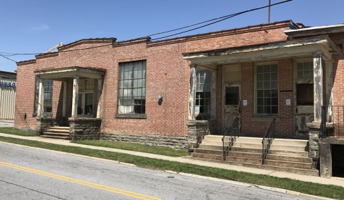 On the left, concrete steps lead to glazed-over-single-panel doors to the original 1915 Entrance to Grey's Hosiery. The low hip roof porticoes are supported by plain square columns. On the right, the 1919 addition mimics the original portico entrance.