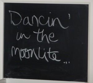 """""""Dancin in the moonlite"""" written on a chalkboard"""