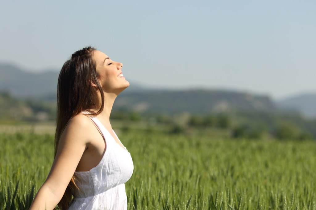 Girl breathing fresh air with white dress in a green wheat meadow