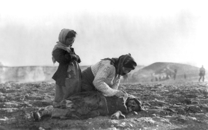 Armenian woman kneeling beside dead child in field, approx. 1917; photo Public Domain, Library of Congress