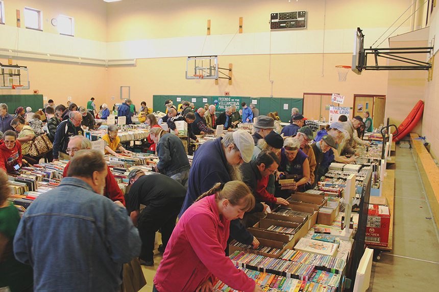 Bibliophiles eagerly pick through stacks of thousands of books hunting for literary treasures at the 2016 Friends of the David and Joyce Milne Public Library; photo courtesy FDJMPL.