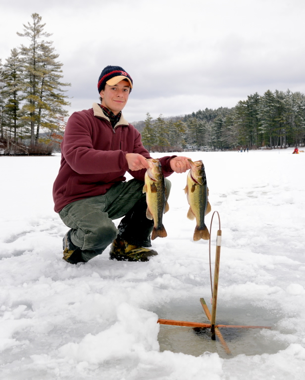 Peter Rawinski at Dean Pond in Oakham, Mass., holding two largemouth bass at a 2013 program; photo courtesy Mass Division of Fish and Wildlife.