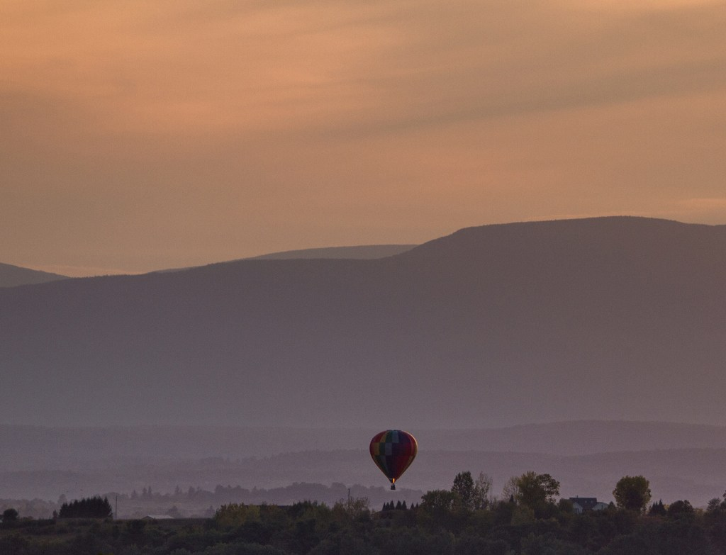 A lonesome balloon glides silently above field and forest near Tice Hill in the Ghent dawn; photo by Zach Neven Creative, Columbia County New York.