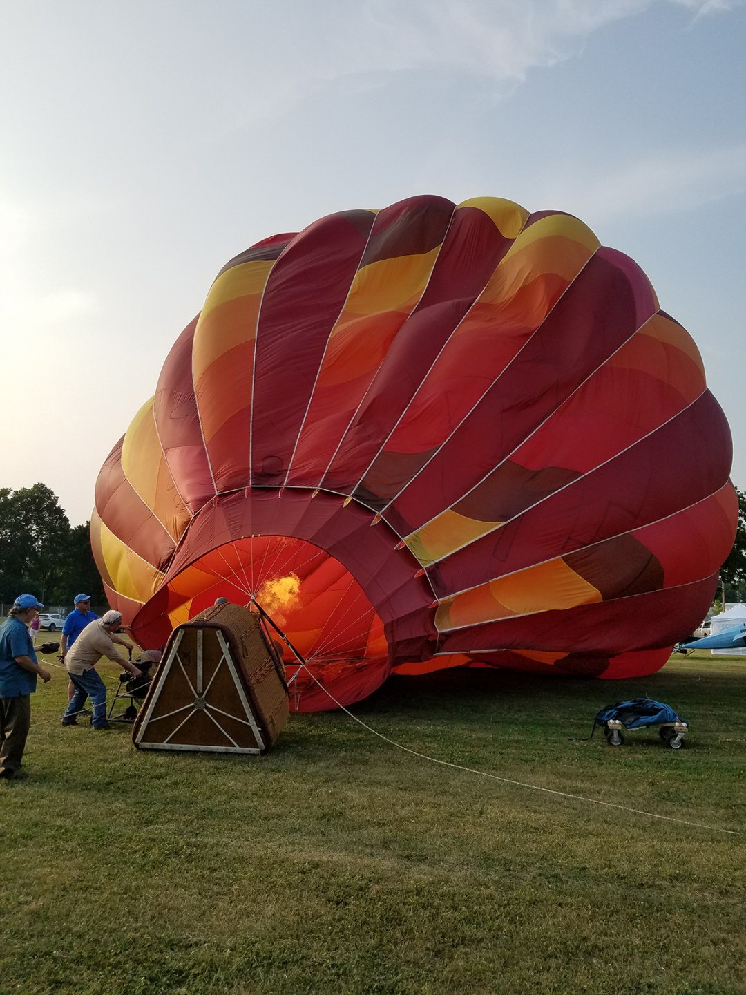 Image of a plume of fire inside a half-inflated hot air balloon on the grounds of the Hudson Valley Hot-Air Balloon Festival days before the event. Caption: A whole lotta heat goes into getting a balloon vertical; photo by Robin Catalano.