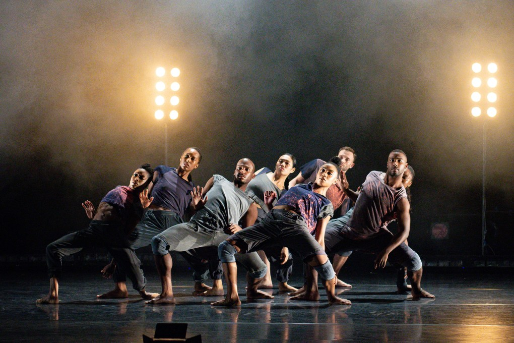 "Photo of a group of eight dancers, in a cluster formation, all in the same pose, leaning backward: A.I.M in ""Drive""; photo by Grace Kathryn Landefeld."