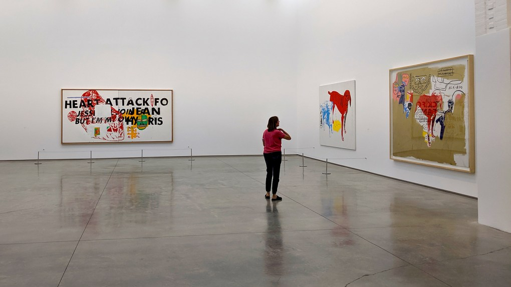 Interior photo of cavernous gallery includes one woman in distance viewing a large painting on a wall; The former Martin Van Buren Elementary School school has ample spatial resources to accomodate Basquiat x Warhol; photo  by Robin-Catalano.