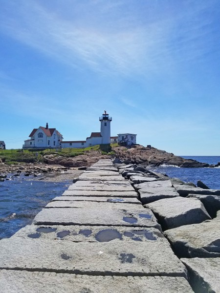 Photo of a stone breakwater (raised wall with smooth top that acts as a pathway) leading to a lighthouse compound; A walk on Dog Bar Breakwater offers panoramic view of the sea and Eastern Point; photo by Robin Catalano.