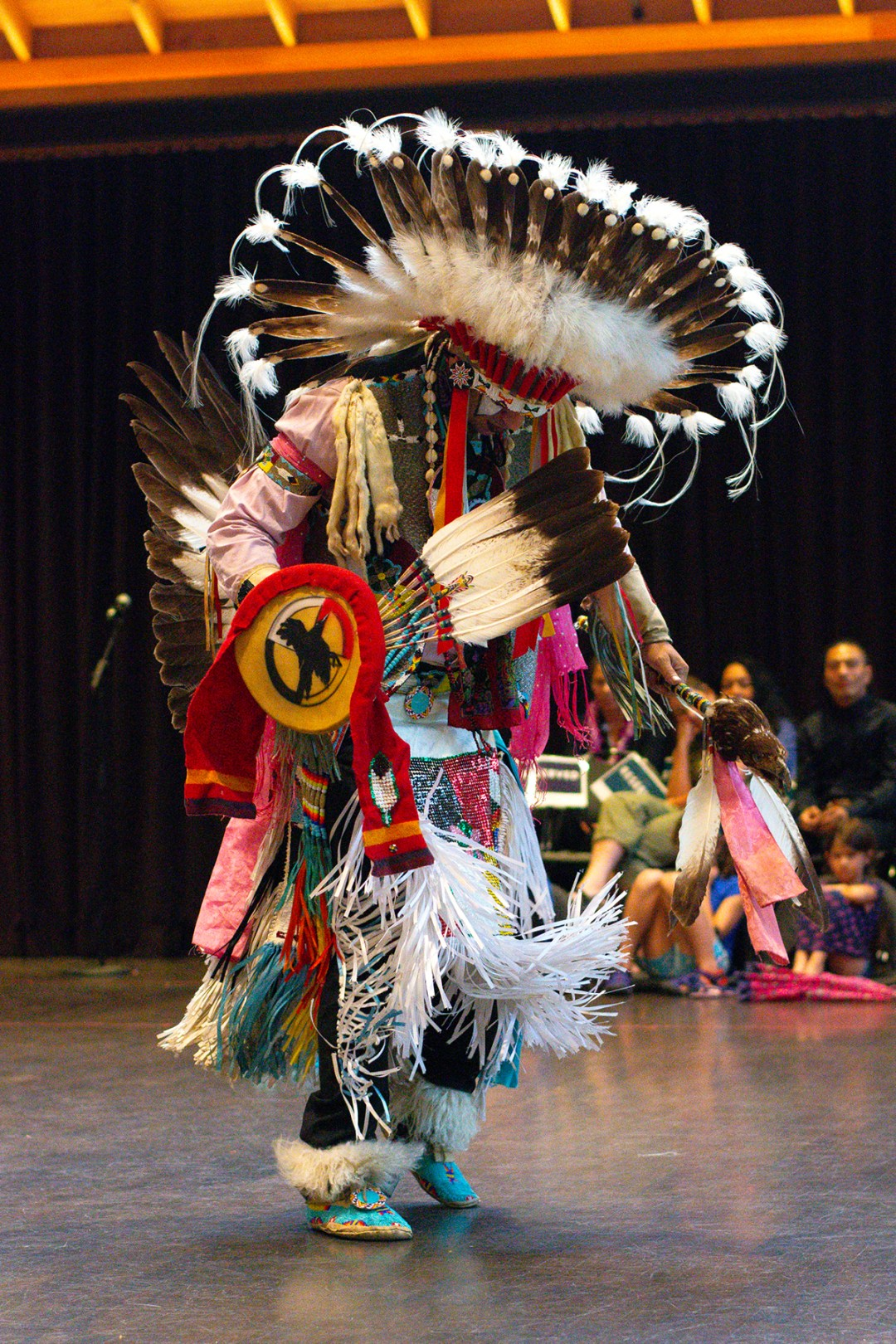 Photo of indigenous American dancer in traditional ceremonial attire: The Land On Which We Dance Inside/Out Performance; photo byGrace Kathryn Landefeld.