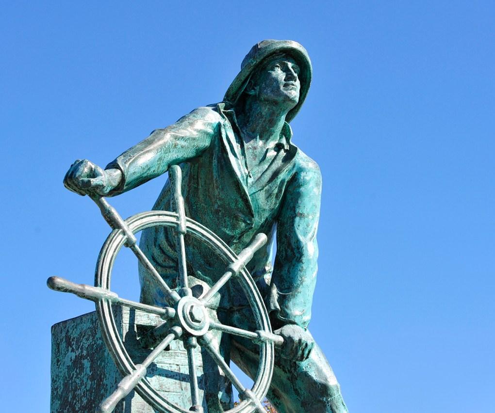 Photo de la célèbre sculpture en plein air du pêcheur tenant une roue de bateau et regardant au loin: la statue de l'homme au volant fait partie du monument commémoratif des pêcheurs de Gloucester. L'artiste Leonard Craske l'a inspiré d'un pêcheur local en 1925; photo gracieuseté de Discover Gloucester.