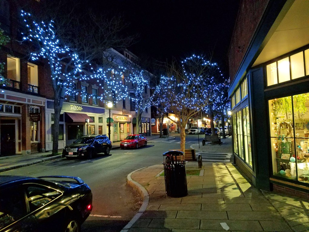 Photo of downtown Gloucester at night. Lights from shop and restaurant windows and decorated trees illuminate the sidewalks:  Just because the sun sets doesn't mean that activity comes to an end — downtown hums with a lively food, music, and arts scene after dark; photo by Robin Catalano.