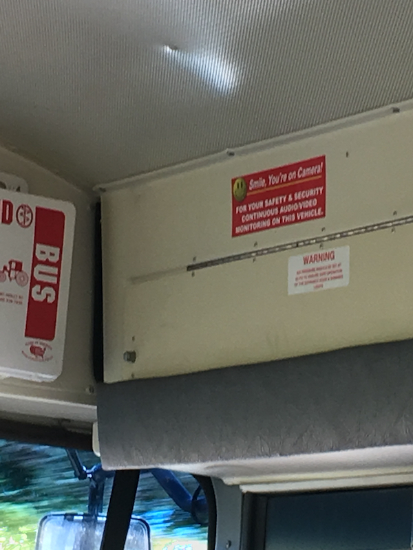 A sticker on the inside of the bus above the front door, where parents are unlikely to see it, is the most public document that describes the use of surveillance cameras.