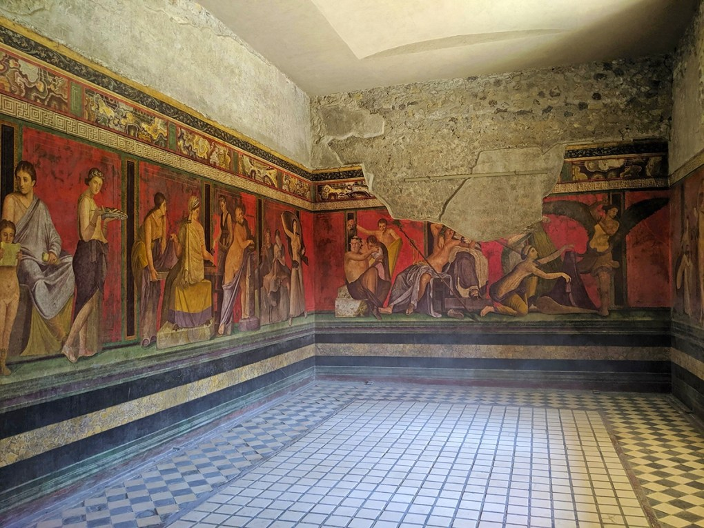 Some of the best-preserved frescoes in Pompeii are found in the Villa de Misteri, or House of the Mysteries. It was named for the large, continuous mural in the dining room, which depicts the initiation ceremony for a Greco-Roman religious cult.