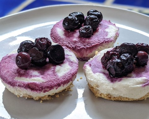 Mini vegan cheesecakes with blueberry topping provide the decadence that let's you close your eyes, savor the smooth sweetness, and pretend for a moment that things are normal; photo by Robin Catalano.