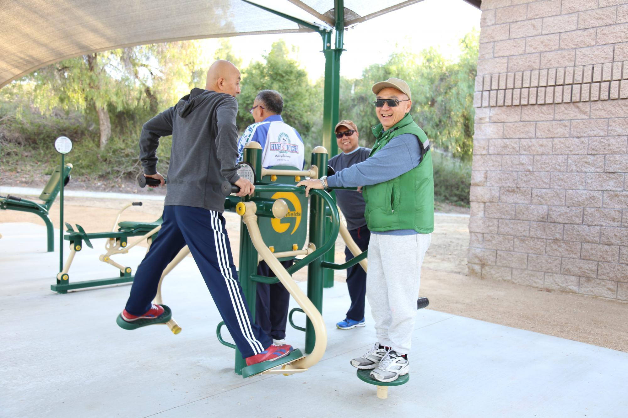 Seniors using outdoor fitness equipment