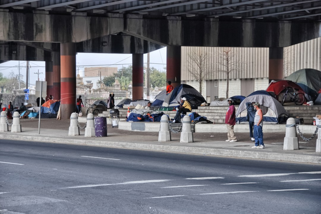 Above: Homeless people prepare to spend the night under a bridge; photo by pisaphotography, via Shutterstock.