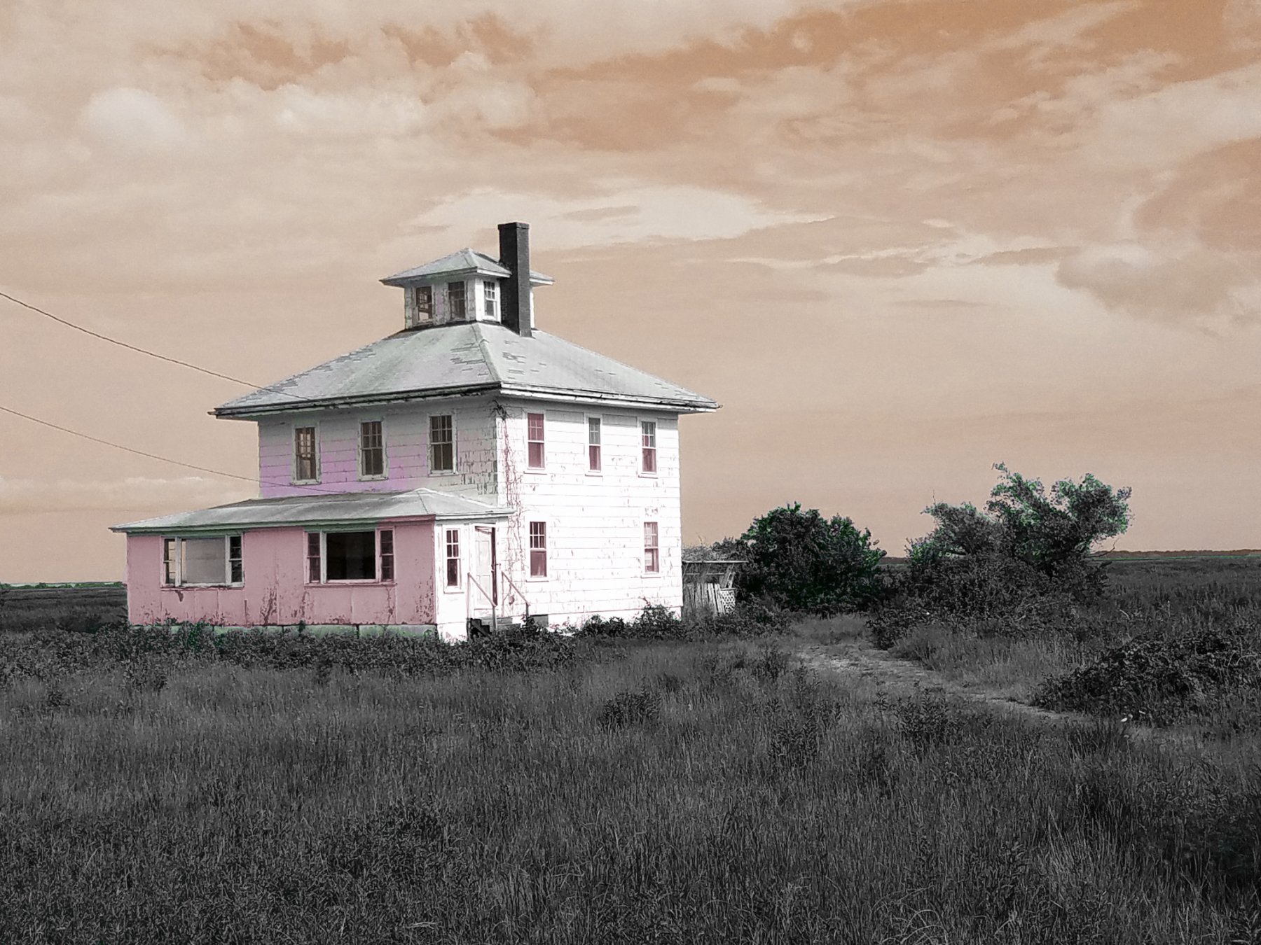 The Pink House waits, perhaps forlorn, perhaps anxious, to find out whether a new chapter awaits its life beside the marshy island shore; photo by Robin Catalano, effects by Jason Velázquez.