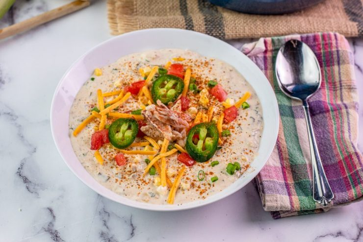 Bowl of creamy white crab chili topped with cheese, corn, jalapeño and tomato