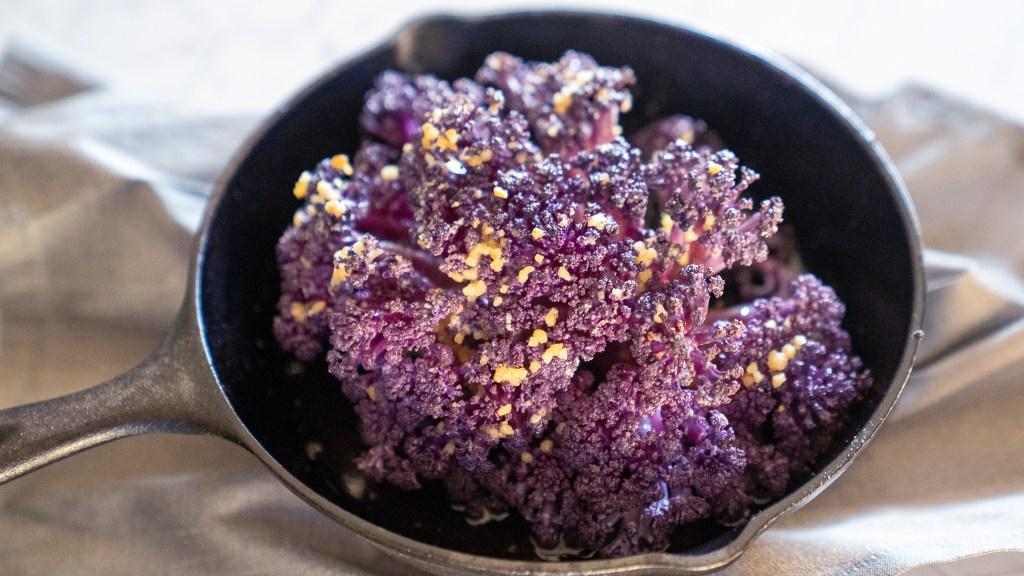 Grilled purple cauliflower on grey background