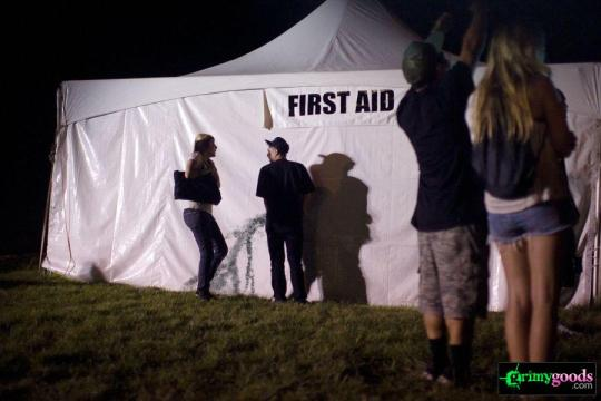 Dude takin' a piss on the First Aid tent while he talks to a girl.