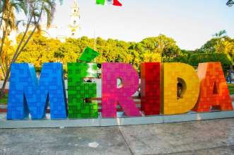 Merida, Mexico. Colorful Merida sign in Plaza Grande. San Ildefonso cathedral in the evening. Mexican flag flutters on air.