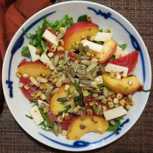Completed salad with corn, pepitas, peaches, mizuna, mozzarella, and beets