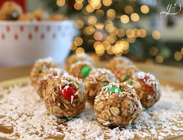 "The BEST 6 Ingredient Christmas Energy Bites | This healthy no bake recipe is easy and quick to prepare. Oatmeal, flaxseed (or hemp seeds), peanut butter, M&Ms, honey, and ""snow"" aka finely shredded coconut make up these homemade gluten free goodies. Make these raw bites for kids and adults alike. Think monster cookie, but with 5 simple whole food ingredients!"