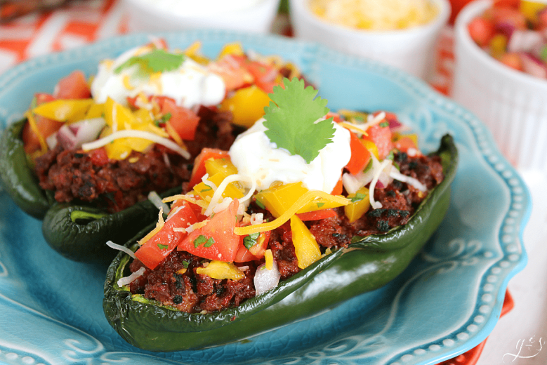 The BEST Clean Eating Stuffed Poblano Peppers | This easy Mexican dinner is healthy, gluten-free, low carb, and keto friendly. Use any ground meat (beef, buffalo, turkey, venison), shredded cheese, and top with a fresh homemade bell pepper salsa. Think of these as a healthy take on tacos by adding plain Greek yogurt (sour cream), avocado, and additional salsa to this delicious recipe. Make Paleo by omitting the cheese or use beans in place of the meat to make it vegetarian!