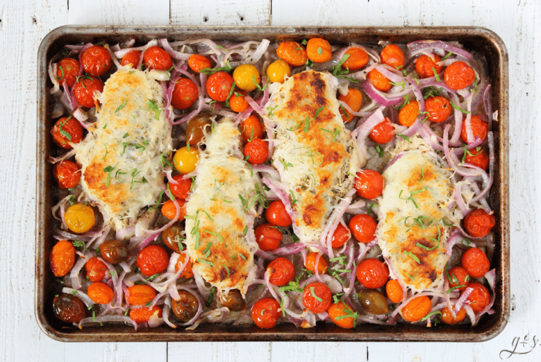 Colorful sheet pan dinner with multi-colored cherry tomatoes, red onions, and chicken with mozzarella cheese.
