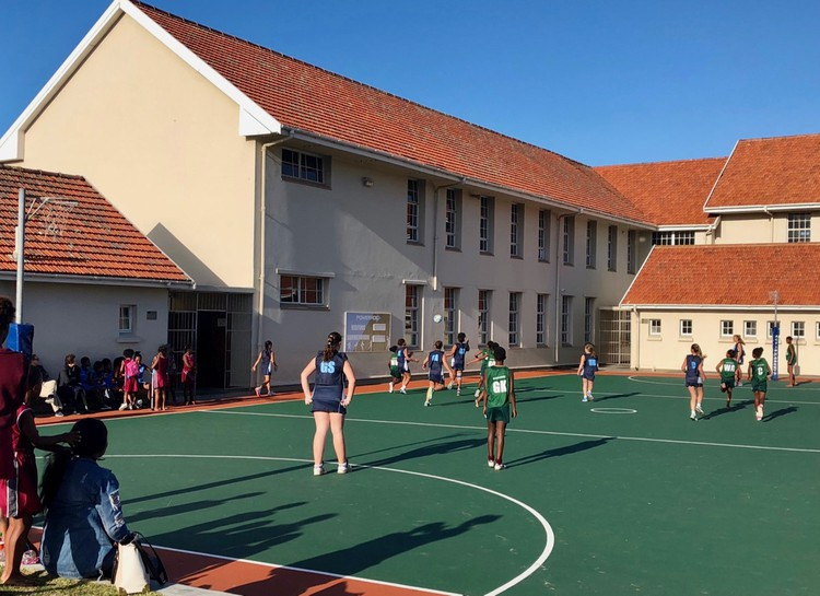 Photo of children playing netball at a school