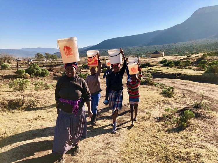 Photo of people walking with buckets on their heads