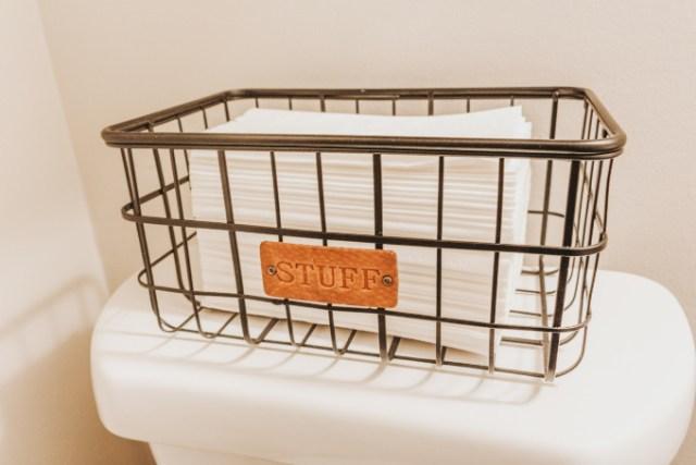 Half bathroom makeover shelving vintage industrial farmhouse decor plants modern tissues in black wire frame basket