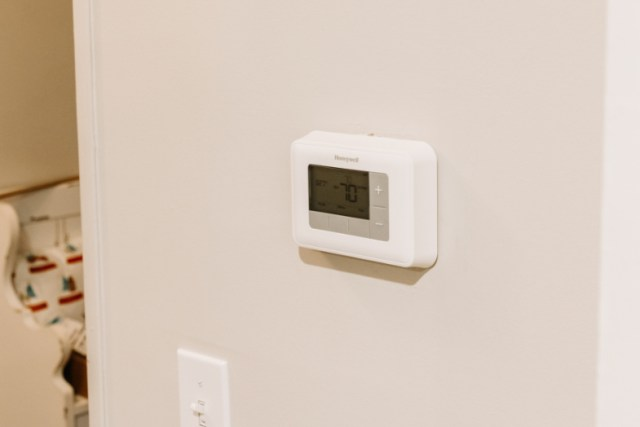 Old Honeywell themostat installed on wall in entryway