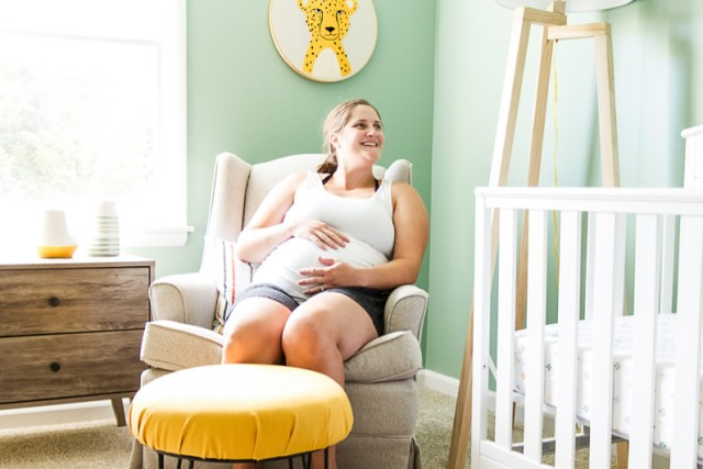 Sitting in glider in baby boy nursery