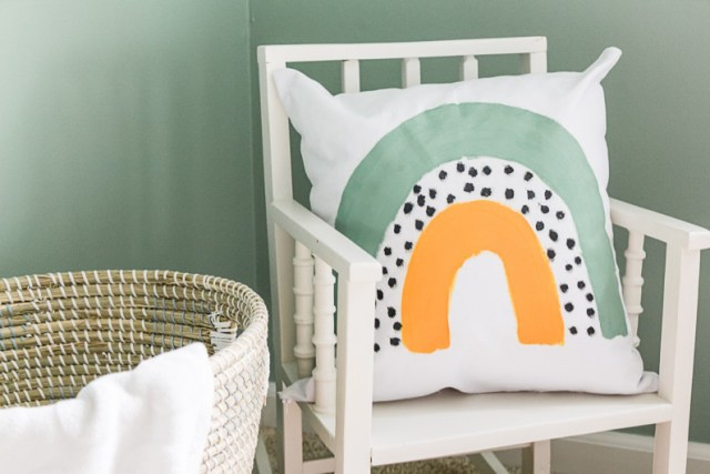 Child sized rocking chair next to basket with DIY fabric painted pillow with rainbow