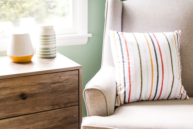 Colorful striped pillow from Target on glider, Wayfair nightstand as side table