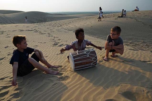Indian boy playing drums in the Rajasthan desert near Jaiselmer